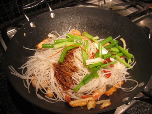 Adding rice sticks and green onions