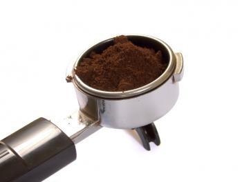 An espresso portafilter with fresh coffee bean grinds.